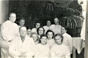 1.r.no kreisās sēž saimniecības vadītājs Mūrmanis, 2.r.no labās Marta Upīte, 2.Vilma Latiševa, aiz viņas pa kreisi augstāk vecmāte Anna Mūrmane, pa kreisi tai blakus Olga Ābola. Aizmugurē no kreisās puses sēž ārsts Jānis Dzirkalis. Foto no B.Puķes arhīva.