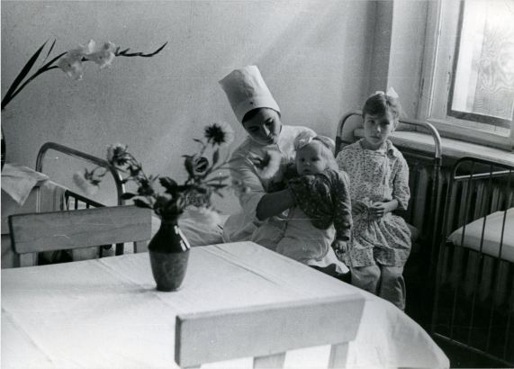 Varakļānu slimnīcas bērnu nodaļa 1960.gads. Ar bērnu klēpī sanitāre Velta Halturina (Varakļānu muzeja krājums)