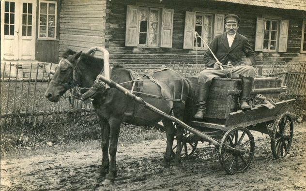 """Meirānu """"Eglaiņu"""" saimnieks Pēteris Krēsliņš ar ratiem, izvedot """"akas"""" (tualetes). 1930.gadi Foto autors nav zināms"""