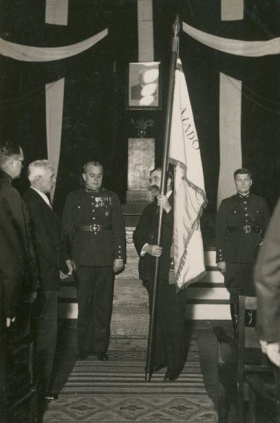 Madonas ģimnāzijas karoga pasniegšana 1939.gada 28.janvārī. Ar karogu direktors Aleksandrs Aizpurītis, no viņa pa kreisi – 9.Madonas aizsargu pulka komandieris Nikolajs Jansbergs. E.Zariņas foto