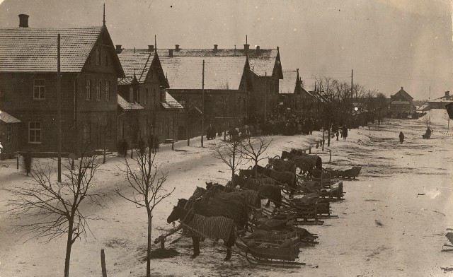 """""""Stāvlaukums"""" Madonā, Rīgas ielā. 1920.gadi. Priekšplānā zirgi, pārsvarā iejūgti kamanās, apsegti ar zirga """"deķiem"""" un piesieti pie slitas (baļķis zirgu piesiešanai pajūgu stāvvietās). Foto autors nav zināms"""