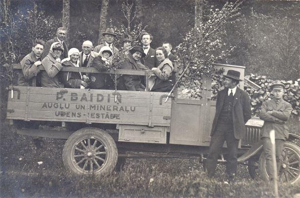 Cilvēku grupa vaļējā smagajā auto. 1930.gadi. Sēd 1.no kreisās komponists Jānis Norvilis. Foto autors nav zināms
