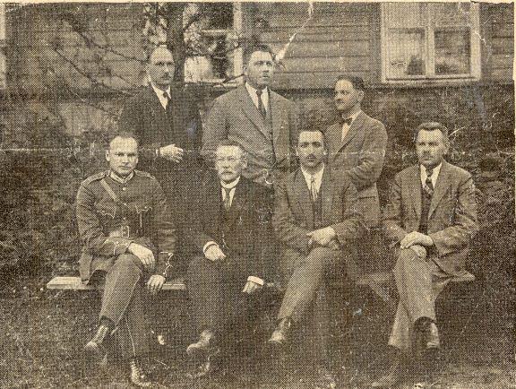 """Madonas apriņķa aptieku īpašnieku un kondicējošo farmaceitu biedrības valdes un revīzijas komisijas locekļi. J.Glīznieka foto. Sēd no kreisās Pēteris Dolmans (Madona), Ansis Vinzarajs (Vestiena), Pauls Baidiņš (Madona), Andrejs Brigaders (Cesvaine), stāv no kreisās Pēteris Kliesbergs (Kraukļi), Otto Leivērs (Dzelzava) (izdevumā uzvārds minēts kļūdaini), Artūrs Grinblats (Vestiena). Žurnāls """"Nedēļa"""", Nr. 40, 1925.gada 2.oktobrī"""