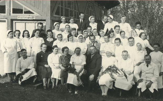 Medicīniskais personāls pie Madonas slimnīcas paviljona. 1943.gads. 1.r. 2.no labās puses sēž Augusts Lapiņš (galvenais ārsts Madonas slimnīcā 1944.-1945.gadā), 4. no labās sēž  Juris Paegle (slimnīcas vadītājs no 1938.-1944.gadam)