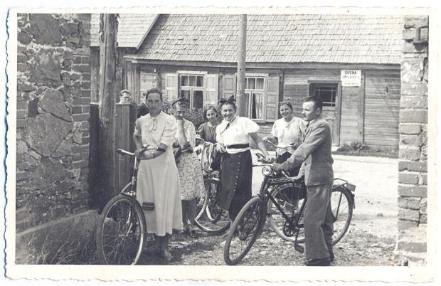 """Sāvienas jaunieši  ar velosipēdiem Ļaudonā. 1930.gadi. Aiz jauniešiem redzama ēka ar izkārtni:""""Šīfera jumtu sedzējs"""". No kreisās Alma Jostiņa. No labās Evalds Cīrulis (Sāvienas ,,Ķunci""""). Foto autors nav zināms"""