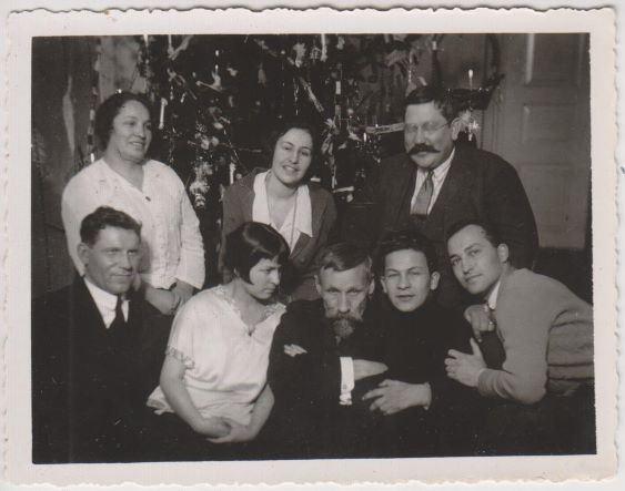 Augusts Saulietis un viesi pie eglītes Lesnieku ģimenē ap 1923.-1925.gadu. 1.rindā: centrā A. Saulietis, 1. no labās Dorihanas dēls Aleksandrs Sosijevs (1901-1971) – mākslinieks. 2.rindā labajā pusē Voldemārs Lesnieks, kreisajā - viņa dzīvesbiedre Dorihana Sosijeva-Lesniece