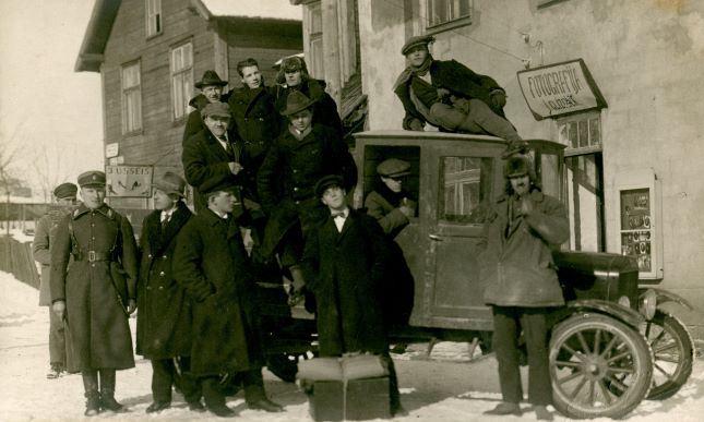 Smagā automašīna pie J.Glīznieka fotodarbnīcas Madonā. 1928.gada 2.janvāris. No labās 2.stāv Pēteris Stepāns (māte Kaileņu skolā strādāja par pavāri). No kreisās augšējā rindā 1.kurpnieks Kažmers (ar platmali). Jāņa Glīznieka foto