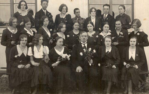 Madonas pilsētas ģimnāzijas izlaiduma klase pie skolas ēkas 1933.gadā.  No kreisās  1.rindā: 3.Marta Aldere, mājturības skolotāja, 4.Aleksandrs Aizpurītis, direktors. No kreisās  2.rindā: Marianna Grundule, Anna Zvirgzdiņa, Berta Zvirgzdiņa, domājams, Šuriņa, ?, ?, ?, Daina Alksne, Lilija Āboliņa. 3.rindā nenoskaidroti absolventi. Otto (Ata) Bērziņa foto